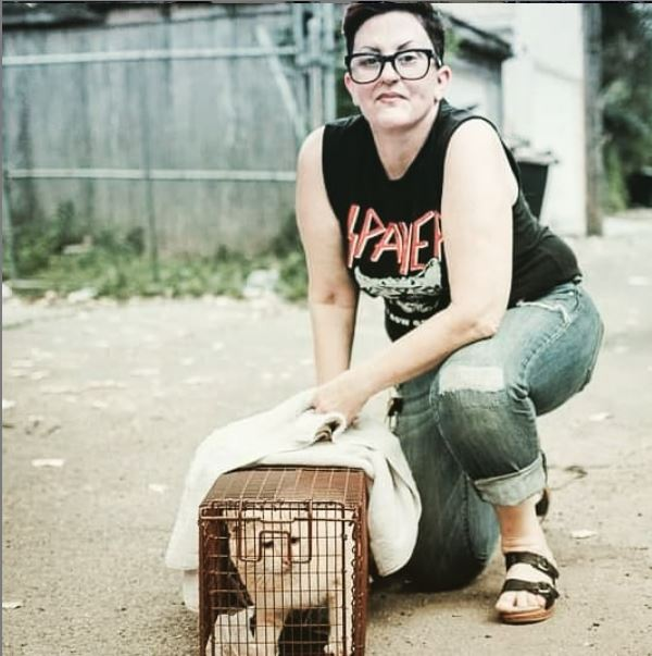 Erica from Cats in Action with a trapped feral cat in a cage outside